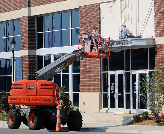 Construction workers complete the trim above the Northeast entrance to the Enid Event Center Tuesday, August 20, 2013. Landscaping has begun on the west side of the new downtown facility near the entrance to Convention Hall. (Staff Photo by BONNIE VCULEK)
