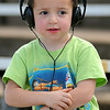 Keaton Brown protects his ears as he watches drivers race at the Enid Speedway Saturday, August 3, 2013. The season-opener is slated for next week. (Staff Photo by BONNIE VCULEK)