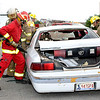 Members of rural fire departments from Garfield County demonstrate how to rescue a person trapped in an automobile during the National Night Out event Tuesday at the Garfield County Courthouse. (Staff Photo by BILLY HEFTON)