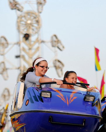 """Chole and Bray Piper hang on  as they ride """"Hurricane"""" Wednesday at Wagner's Carnival in the Oakwood Mall parking lot. (Staff Photo by BILLY HEFTON)"""