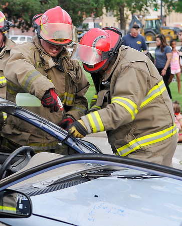 Members of the Kremlin Fire Department use a hacksaw to remove the top of an automobile demonstrating the old fashion was of rescuing a person trapped after an accident during the National Night Out event Tuesday at the Garfield County Courthouse. (Staff Photo by BILLY HEFTON)
