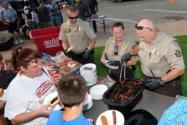 garfield County deputies serve hot dogs during the National Night Out event Tuesday at the Garfield County Courthouse. (Staff Photo by BILLY HEFTON)
