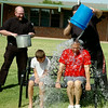 Father Carson Krittenbrink (left) laughs as Father Joseph Irwin (top right)drenches Dominic Bocox and Deacon Tony Crispo (seated, from left) during an ALS Ice Challenge at St. Joseph Catholic School Friday, August 22, 2014. Students' donations filled a five-gallon bucket as Deacon Crispo vowed to match the donations for John Paul II Medical Research Institute, whose research uses adult stem cells and is pro-life driven. (Staff Photo by BONNIE VCULEK)