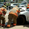 Enid firefighters assist as Enid Police Officers investigate a multi-vehicle accident at the intersection of West Broadway and Van Buren Friday, August 22, 2014. (Staff Photo by BONNIE VCULEK)