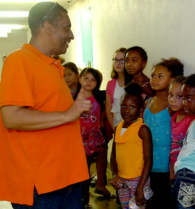 Rev. Carlton Burton, from Zoe Bible Church, gives instructions to the older children at the Kid's Cafe mentoring program Wednesday, August 27, 2014. The church's non-profit, Christian-based mentoring is Monday-Friday from 3:30-6 p.m. Children receive an after-school snack, complete homework assignments, watch a movie or play games each day. (Staff Photo by BONNIE VCULEK)