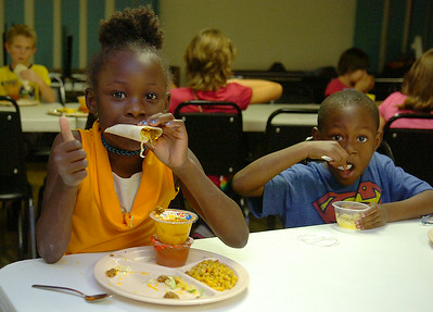 Navaeh Smith (left) and her younger brother, A.J., enjoy turkey tacos, corn, and fresh fruit during the Zoe Bible Church Kid's Cafe Wednesday, August 27, 2014. The non-profit, Christian-Based activities are Monday-Friday, from 3:30-6 p.m. (Staff Photo by BONNIE VCULEK)