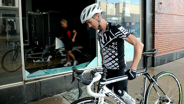 An AMBUCS Twilight Criterium competitor carries his bike past broken glass as AMBUCS member clean up the damage at The Chiropractic Center after two large glass panels blew out as heavy rain and hail moved through downtown Enid Saturday, August 16, 2014. (Staff Photo by BONNIE VCULEK)