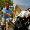 Ryan Beckham, from Crossroads Roofing Supply, places squares of Highlander shingles onto a conveyor at a new home in Chisholm Creek Village Wednesday, August 27, 2014. (Staff Photo by BONNIE VCULEK)