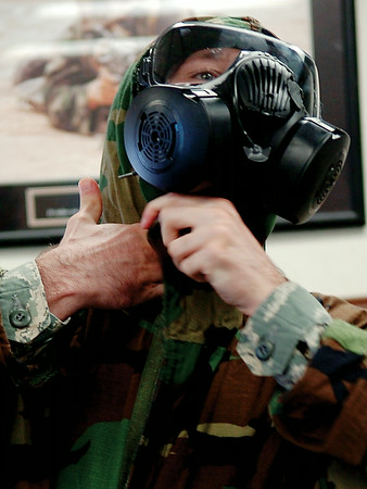 Airman Joshua Daggett dons a chemical suit during a demonstration in the Logistics Readiness Squadron facility at Vance Air Force Base Wednesday, August 20, 2014. Daggett, a member of the 71st Flying Training Wing's Emergency Management Squadron, is following in his father's career footsteps. (Staff Photo by BONNIE VCULEK)