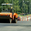 A road repairman uses an asphalt roller along Broadway Friday, August 01, 2014. (Staff Photo by BONNIE VCULEK)
