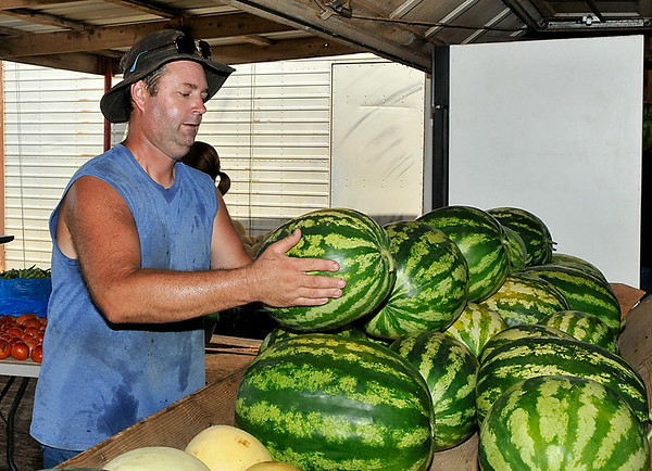 Ryan Koehn stacks a watermelon at the K&S Produce stand east of Ringwood Saturday. (Staff Photo by BILLY HEFTON)