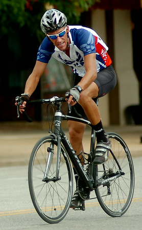 Team Vance's Matt Bell competes in the AMBUCS Twilight Criterium in downtown Enid Saturday, August 16, 2014. After falling twice during the short course race when heavy rain and hail started to fall, Bell and another Team Vance member placed first and second in the event. (Staff Photo by BONNIE VCULEK)