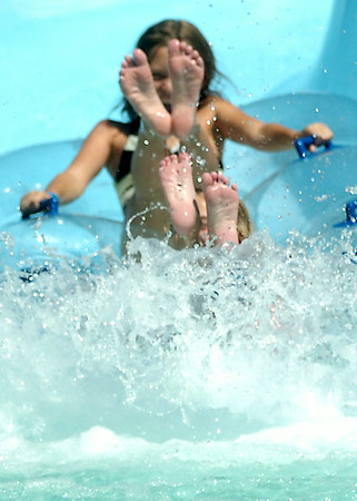 Feet fly into the air as Katelyn Reames and Reagan McDaniel tube the Zinger at Splash Zone Saturday, August 9, 2014. With several schools beginning classes in the next two weeks, children and their parents are taking breaks from the summer heat. (Staff Photo by BONNIE VCULEK)