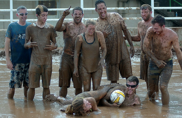 The Muddy Badgers, from Oklahoma City, celebrate their Enid Miracle League Mud Volleyball championship at the Garfield County Fairgrounds Saturday, August 02, 2014. Proceeds from the event benefit Miracle League baseball for children and adults with special needs. (Staff Photo by BONNIE VCULEK)