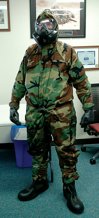 Airman Joshua Daggett dons a chemical suit during a demonstration in the Logistics Readiness Squadron facility at Vance Air Force Base Wednesday, August 20, 2014. Daggett, a member of the 71st Flying Training Wing Emergency Management Squadron, is following in his father's career footsteps. (Staff Photo by BONNIE VCULEK)