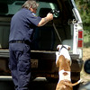 An Enid Animal Control officer places a canine into his vehicle as the Enid Police Department completes a narcotics warrant search at 424 S. Monroe Thursday, August 14, 2014. (Staff Photo by BONNIE VCULEK)
