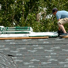 A young man places Highlander shingles on the roof of a new home at 4813 Beckett in the Chisholm Creek Village Wednesday, August 27, 2014. (Staff Photo by BONNIE VCULEK)
