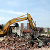 Convention Hall and Enid Event Center appear in the background, as a T. & J. Demolition heavy equipment operator removes a building on the west side of Grand Tuesday, August 05, 2014. (Staff Photo by BONNIE VCULEK)