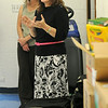 Becky Bules (back left) listens, as April Danahy, human resources and public relations director for Security National Bank, discusses the different back-to-school supplies that were collected and delivered to Adams Elementary School teachers Friday, August 15, 2014. (Staff Photo by BONNIE VCULEK)