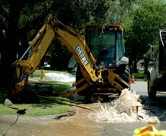 City of Enid Water Reclamation Services employees flow a fire hydrant on the corner of S. Quincy and W. Oklahoma as they repair a water line break Tuesday, August 19, 2014. (Staff Photo by BONNIE VCULEK)
