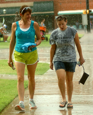 Drenched spectators at the AMBUCS Twilight Criterium bicycle races seek shelter as heavy rain and hail falls in downtown Enid. Races were delayed as a severe thunderstorm dropped over one-half inch of rain and up to quarter-size hail as it moved across the downtown area. (Staff Photo by BONNIE VCULEK)