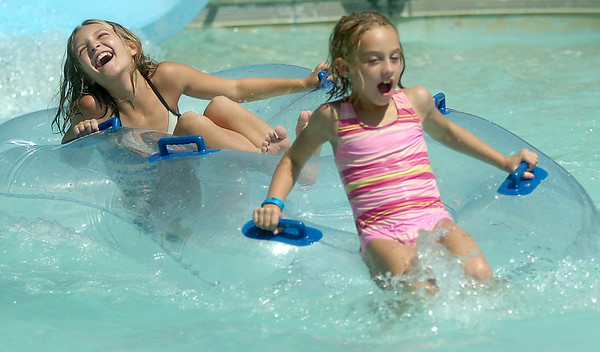 Reagan McDaniel and Katelyn Reames (from left) react as they tube the Zinger at Splash Zone Saturday, August 9, 2014. With several schools beginning classes in the next two weeks, children and their parents are taking breaks from the summer heat. (Staff Photo by BONNIE VCULEK)