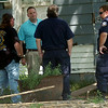 Det. Bryan Hart (back center) visits with other law enforcement officers following an Enid Police Department narcotics search at 424 S. Monroe Thursday, August 14, 2014. (Staff Photo by BONNIE VCULEK)