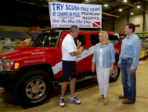 Jerry Coleman, from Into the Blue Dive Shop, LLC, visits with Okla. Gov. Mary Fallin and her husband Wade Christensen during Gov. Fallin's campaign bus tour to the KNID Sportsman's and Outdoor Expo in Enid Saturday, August 23, 2014. (Staff Photo by BONNIE VCULEK)