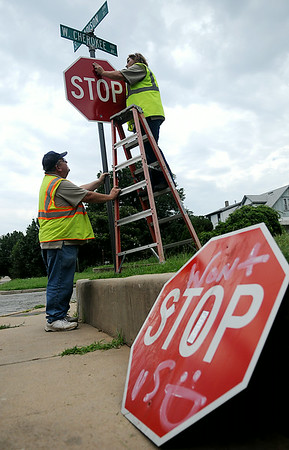 Michael Goodpasture and Karen Hackett, with the city of Enid Public Works Traffic Division, remove and replace graffiti-clad signs around Enid Wednesday, August 6, 2014. (Staff Photo by BONNIE VCULEK)