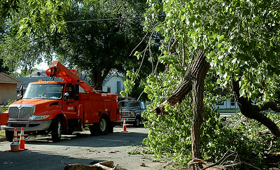 A severe thunderstorm's high winds damaged trees near the Garfield/Maple intersection causing power outages to several Enid residents late Monday, August 18, 2014. OG&E line crew technicians worked through the night and completed repairs in the area Tuesday morning. (Staff Photo by BONNIE VCULEK)