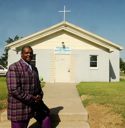 Rev. Barry Robinson pauses in front of Progressive Missionary Baptist Church Sunday, August 28, 2014. After the church moved to 12th and Ash,  the city of Enid said the church would have to pay for another water line installation to build a new sanctuary, but later re-tested and the church may expand when funds are available. (Staff Photo by BONNIE VCULEK)