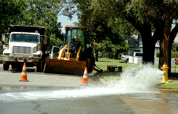 A fire hydrant flows as city of Enid employees repair a water line break near the intersection of S. Quincy and W. Oklahoma Tuesday, August 19, 2014. (Staff Photo by BONNIE VCULEK)