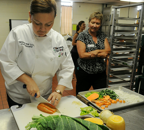 Tiffany Poe, a chef educator with Cooking for Kids demonstrates the proper way to cut a sweet potato during a two-day seminar at Enid Public Schools' Central Kitchen Thursday, August 14, 2014. (Staff Photo by BONNIE VCULEK)