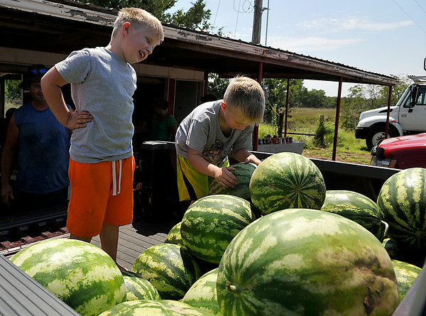 Eli and Noah Koehn help to unload a truckload of watermelons at the K&S Produce stand east of Ringwood Saturday. (Staff Photo by BILLY HEFTON)