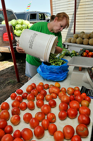 Donna Smith refills the okra bucket at the K&S Produce stand east of Ringwood Saturday. (Staff Photo by BILLY HEFTON)
