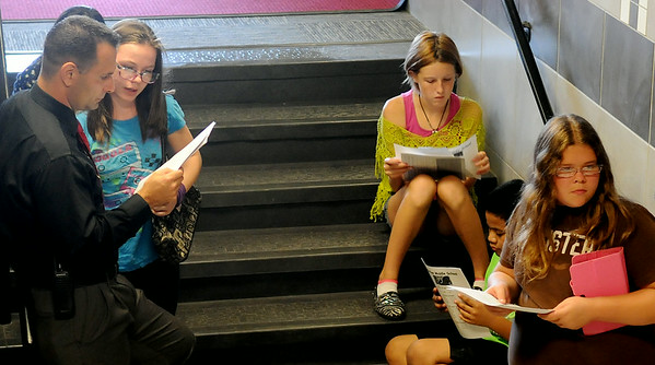 """Longfellow Middle School principal Scott Fitzgerald assists sixth-grade students with their schedules during the """"Saddle Up"""" orientation Wednesday, August 13, 2014. Events were held at Emerson, Longfellow and Waller to welcome new students to the middle schools. (Staff Photo by BONNIE VCULEK)"""