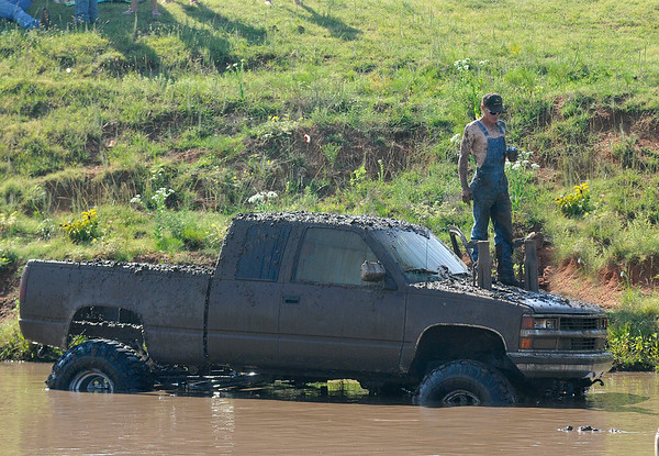 A competitor stnads on the hood of his truck after stalling in a pond during Molly Mayhem's Mud Bog Saturday August 9 in Hennessey. (Staff Photo by BILLY HEFTON)