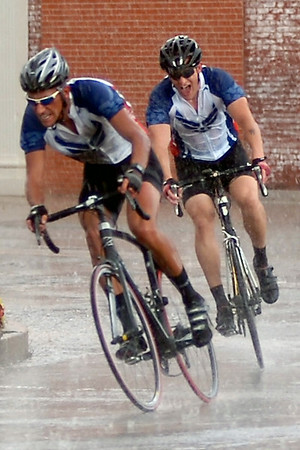 Two Team Vance riders battle heavy rain and hail as they sprint through the final lap of the Tour de Trykes Twilight Criterium Men's Open in downtown Enid, Saturday, August 16, 2014. The riders finished one-two.(Staff Photo by BONNIE VCULEK)