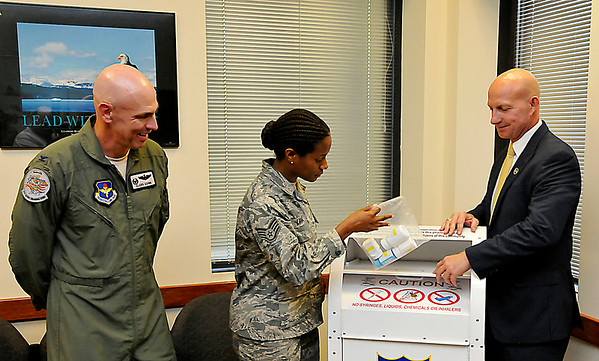 New Vance Wing Commander, Col. Clark Quinn (left) and Oklahoma Bureau of Narcotics director, Darrell Weaver (right), watch as Investigator Remmecya Lavant deposits a bag of perscription drugs into a collection Monday at the Vance Air Force Base Visitor's Center. (Staff Photo by BILLY HEFTON)