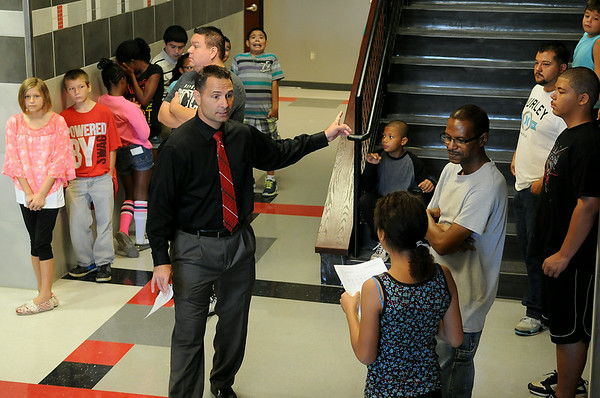 """Sixth-grade students wait outside the Longfellow Middle School office for their schedules as LMS Principal Scott Fitzgerald directs another student to her classrooms during """"Saddle Up"""" orientation Wednesday, August 13, 2014. (Staff Photo by BONNIE VCULEK)"""