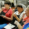 Enid Public Schools' nutrition professionals listen as they sample a variety of fresh fruits and vegetables during a Cooking for Kids seminar at Central Kitchen Thursday, August 14, 2014. (Staff Photo by BONNIE VCULEK)