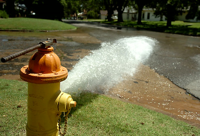 A fire hydrant flows at the intersection of S. Quincy and W. Oklahoma as the city of Enid water reclamation service employees repair a water main break Tuesday, August 18, 2014. (Staff Photo by BONNIE VCULEK)