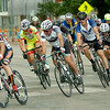 The Men's Open pack sprints around the corner at Broadway and Grand as heavy rain begins to fall during the AMBUCS Twilight Criterium in downtown Enid Saturday, August 16, 2014. Team Vance riders finished one-two in the race. (Staff Photo by BONNIE VCULEK)