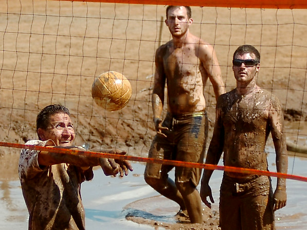 A Muddy Badgers' defender (left), from Oklahoma City, concentrates during a return against the Rum Boats, from Enid, during the Enid Miracle League Mud Volleyball Tournament championship finals at the Garfield County Fairgrounds Saturday, August 02, 2014. Funds raised during the event support the Miracle League baseball teams for children and adults with special needs. (Staff Photo by BONNIE VCULEK)