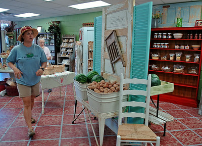Paulette Rink (left), with Rowdy Stickhorse Farm to Fork Market, helps her customers inside their new business location at 1923 W. Owen K. Garriott in Indian Hills Shopping Center Saturday, August 30, 2014. (Staff Photo by BONNIE VCULEK)