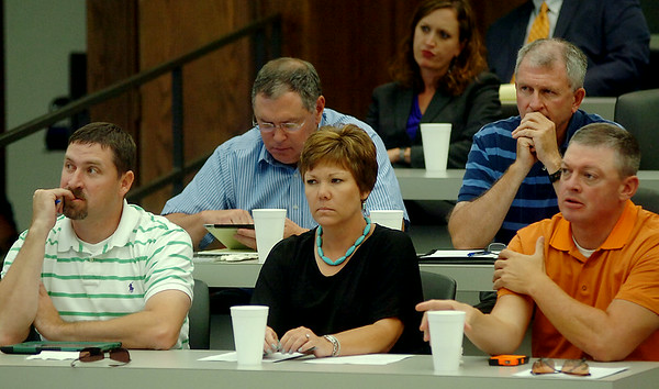Individuals listen during the 2014 Farm Bill Symposium sponsored by Philip J. Outhier, Attorney at Law and Partner with Outhier & Caruthers PLLC, at Autry Technology Center Wednesday, August 13, 2014. Guest speakers were Jeremy S. Bennett, a Field Representative for Congressman Frank Lucas, and Dr. Jody Campiche from Oklahoma State University.  (Staff Photo by BONNIE VCULEK)