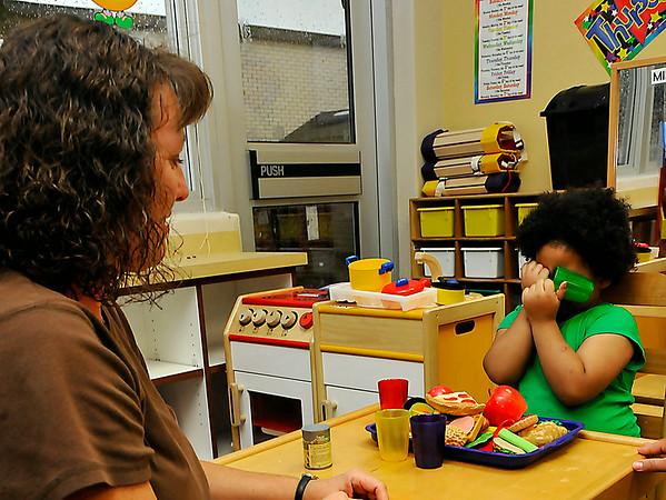 Jasmine Gordon hides her face as she works with kindergarten teacher, Annemarie Miller, during Meet the Teacher night at Monroe Elementary Monday. (Staff Photo by BILLY HEFTON)