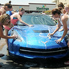 Pioneer High School cheerleaders wash a new 2014 Corvette as they raise money for new uniforms at Sunset Plaza Saturday, August 9, 2014. (Staff Photo by BONNIE VCULEK)