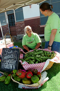 Barbara Freed (back left) and Kim Houk (right), with Freed Family Farms, have a variety of vegetables for Enid Farmers Market customers Saturday, August 30, 2014. (Staff Photo by BONNIE VCULEK)