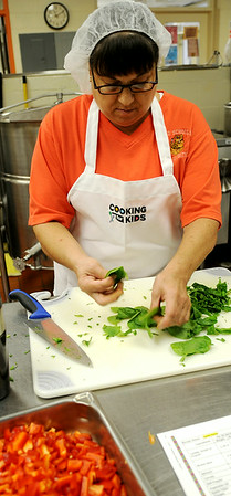 Cheryl McFarland prepares ingredients for a recipe during Cooking for Kids at Enid Public Schools' Central Kitchen Friday, August 15, 2014. (Staff Photo by BONNIE VCULEK)